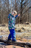 A boy climbs on a tree. In the spring forest Stock Photos