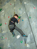 A boy climbs a wal. L holding on to clip Stock Photography