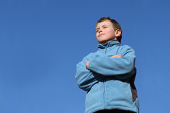 Boy with closed eyes in blue jacket, blue sky Stock Photos