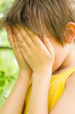 Boy closed face with his hands. Portrait of little boy closed face with his hands Royalty Free Stock Images