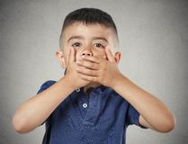 Boy closing, covering mouth with hands Royalty Free Stock Photos