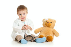 Boy with clothes of doctor and teddy bear. Adorable boy with clothes of doctor isolated on white Royalty Free Stock Photos