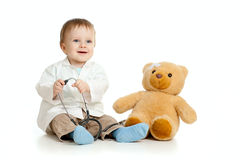 Boy with clothes of doctor and teddy bear. Adorable boy with clothes of doctor isolated on white Stock Photography
