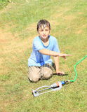 Boy in clothes playing with sprinkler Stock Photos