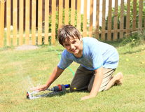 Boy in clothes playing with sprinkler Stock Image