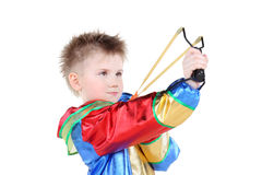 Boy in clown costume holds slingshot and aims up. Isolated on white background Stock Photography