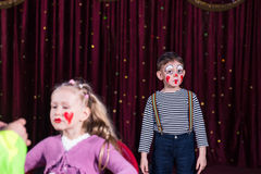 Boy Clown and Girl Having Makeup Applied on Stage Stock Images