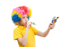 The boy in clown wig with wooden toys and whistle Stock Images