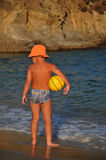 Boy on the coast with the ball. Boy in a bathing on the coast with the ball Stock Image