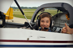 Boy in Cockpit of Airplane. A young boy gets to sit in the cockpit of an airplane at the Wings and Wheels event at the Kenosha Airport in Kenosha, Wisconsin Royalty Free Stock Image