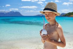 Boy with coconut on turquoise beach Stock Image