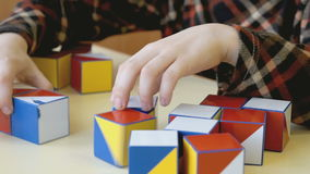 Boy collecting a pattern using colored cubes