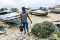 A boy collecting water on the beach in front of a fishing village in Negombo, Sri Lanka. Royalty Free Stock Photos