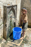 A boy collecting water from a fountain at the entrance to the Fez medina in Morocco. Royalty Free Stock Photos