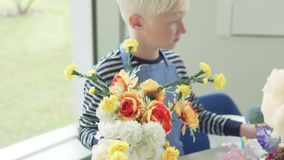 A boy collects a bouquet of artificial flowers in the children`s city stock video footage