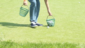 The boy collects golf balls stock footage