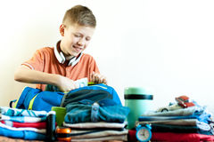 The boy collects his things on the trip royalty free stock image