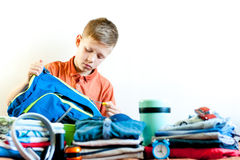 The boy collects his things on the trip royalty free stock photo