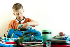 The boy collects his things on the trip stock photography