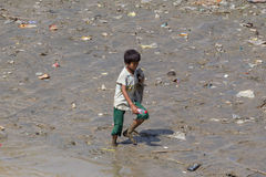 A boy collects plastic bottles on the banks of the Yangon River, Myanmar Royalty Free Stock Image