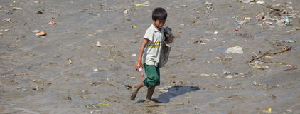 A boy collects plastic bottles on the banks of the Yangon River, Myanmar Stock Photos