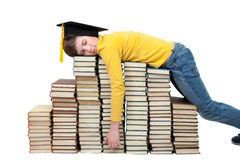 A boy with collegiate cap sleeping on a stack of books Royalty Free Stock Image
