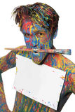 Boy in color. Male model covered in paint with brush and blank paper Royalty Free Stock Image
