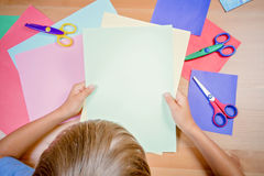 Boy with color paper and scissors making greeting card Royalty Free Stock Image