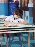Boy With Color Pencils Drawing In Classroom Stock Photography