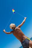 Boy with colorful kite against blue sky at the beach. Boy playing with colorful kite against blue sky at the beach Royalty Free Stock Images