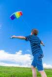 Boy with colorful kite on the green hill Royalty Free Stock Photo