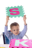 Boy with colorful letters in raised hands Royalty Free Stock Image