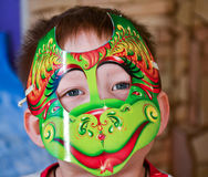 Kid with mask. Kid in a colorful mask looks at the camera Royalty Free Stock Photography