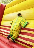 The boy in colorful plastic dress in the bouncy castle Stock Image