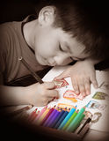 Boy coloring. Boy concentrate on coloring picture stock photography