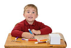 Boy Coloring. Child, with a goofy expression, coloring with markers, isolated on white Royalty Free Stock Photos