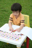 Boy coloring. Boy happily coloring with crayon Royalty Free Stock Image