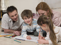 Boy Coloring Pictures While Family Looking At It On Floor. Portrait of cute boy coloring pictures while family looking at it on floor Royalty Free Stock Images
