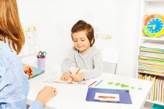 Boy colors shapes during ABA with therapist near Stock Photography