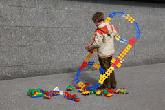 Boy with coloured toy railway and trains Royalty Free Stock Photos