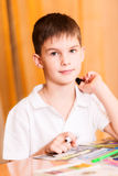 Boy colouring book portrait. Boy colouring book looking at camera Royalty Free Stock Photo