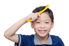Boy combs his hair by yellow comb. Asian boy combs his hair by yellow comb over white Royalty Free Stock Photography