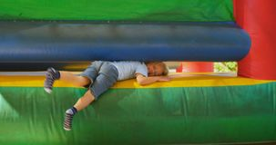 Boy coming out from bouncing castle 4k. Boy coming out from bouncing castle in the playground 4k stock footage