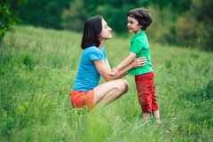 The boy communicates with his mother in nature. A women listens to her son. Walk with the baby through the meadow. The kid is talking to mom. A women is Stock Photos