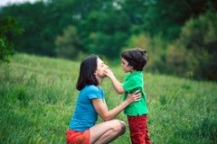 The boy communicates with his mother in nature. A women listens to her son. Walk with the baby through the meadow. The kid is talking to mom. A women is Royalty Free Stock Photo