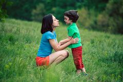 The boy communicates with his mother in nature. A women listens to her son. Walk with the baby through the meadow. The kid is talking to mom. A women is royalty free stock image