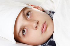 Boy with the compress preparing for treatment procedures. Boy with the flu and compress preparing for treatment procedures Stock Images