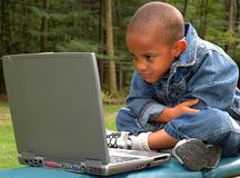 Boy on Computer. A child surfing the internet using a wireless connection outdoors Stock Images