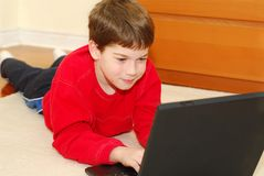 Boy computer. Young boy lying on the floor with portable computer Royalty Free Stock Image