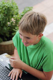 Boy on Computer. A child surfing the internet using a wireless connection outdoors Royalty Free Stock Images